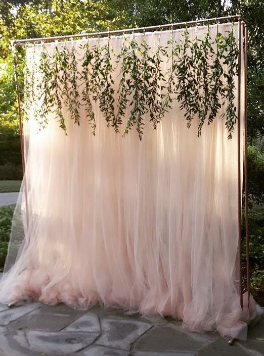 Pink tulle backdrop with greenery